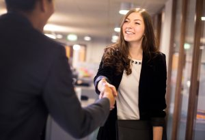 young woman arrives at her interview , resume under her arm greeting her interviewer